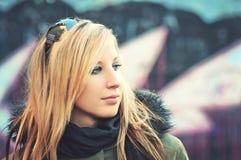 Hübsche Frau, die vor Graffitiwand steht lizenzfreie stockfotos