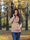 Hübsche Frau, die am Waldland während des Herbstes aufwirft Lizenzfreies Stockbild