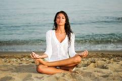Hübsche Frau, die Yoga auf dem Strand tut stockfotos