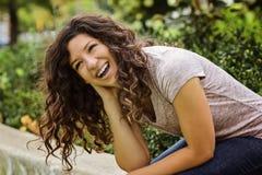 Hübsche Frau, die zufällig in der Park-Einstellung lacht Lizenzfreie Stockfotos