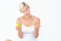 Hübsche Frau, die zwischen Pizza und Apfel entscheidet Stockbild