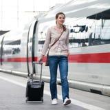 Hübsche Frau an einem Bahnhof stockfotografie