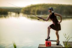 Hübsche Frau in einem Burgunder-Kleid und schwarzen Schuhe und eine Baseballmütze fängt Fische auf einem hölzernen Pier lizenzfreies stockfoto