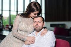 Hübsche Frau in einem Glättungskleid hält Mann in einem weißen Hemd und in den Küssen stockfotografie