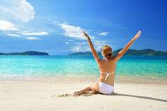 Hübsche Frau in einer guten Laune, die auf dem weißen sandigen Strand sich sonnt Lizenzfreies Stockbild