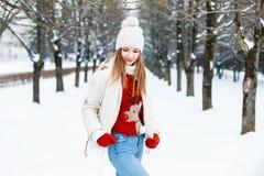Hübsche Frau in einer roten Strickjacke, in einer weißen Kappe und in einer Jacke, gestrickt Lizenzfreies Stockbild