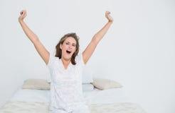 Hübsche Frau im ausdehnenden Bett beim Aufwachen lizenzfreie stockbilder