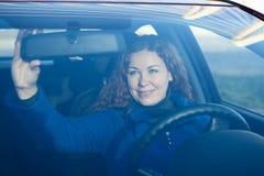 Hübsche Frau im Auto, das zum Antreiben sich vorbereitet Stockbild