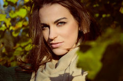 Hübsche Frau im beige Schal lächelnd auf sonnigem Stockfoto