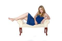 Hübsche Frau im blauen Kleid, das auf Bank lounging ist stockbild