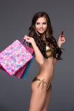 Hübsche Frau im Goldbikini, der Einkaufstaschen hält Stockfoto