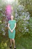 Hübsche Frau im grünen Kleid steht nahe blühender Flieder Lizenzfreies Stockfoto
