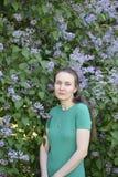 Hübsche Frau im grünen Kleid steht nahe blühender violetter Flieder Lizenzfreies Stockfoto