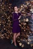 Hübsche Frau im Kleid steht im Studio mit Kamin Stockfoto
