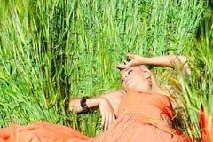 Hübsche Frau im orange Kleiderlügen Lizenzfreie Stockfotos