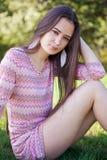 Hübsche Frau im Park, der auf Gras sitzt Lizenzfreies Stockfoto