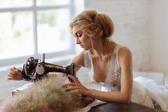 Hübsche Frau Im Stil Coco Chanels, die auf einer Nähmaschine sitzt lizenzfreie stockbilder