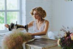 Hübsche Frau Im Stil Coco Chanels, die auf einer Nähmaschine sitzt lizenzfreie stockfotos