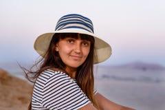 Hübsche Frau im Strand-Hut lächelnd an der Kamera lizenzfreies stockbild