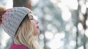 Hübsche Frau im Winterhut genießt die stehende Außenseite des Schnees auf dem Schnee im Wald sie das Lächeln und atmet tief ein stock video