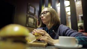 Hübsche Frau isst geschmacklosen Burger und Pommes-Frites in im schlechten Café und dem Fühlung Junges Mädchen in den Gläsern ist stock video footage