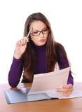 Hübsche Frau ist Lesedokument und -c$denken Lizenzfreie Stockfotografie