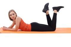 Hübsche Frau in Lügentrainingsbeinen der Sportkleidung auf einer Matte stockfoto