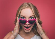 Hübsche Frau mit blondes Haar weard Sonnenbrille mit rosa Rand Sie schaut auf Kamera und hält Gläser am eage Stockfotografie