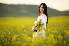 Hübsche Frau mit Blumenstrauß von Wildflowers auf dem gelben Gebiet im Sonnenuntergang beleuchtet, Sommerzeit Lizenzfreie Stockfotos