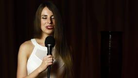 Hübsche Frau mit dem erstaunlichen langen gewellten Haar hält mic und singt mit hellem Lächeln stock video footage