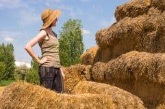 Hübsche Frau mit dem Hut, der mit den Händen auf ihrer Taille nahe Strohballen steht Stockbilder