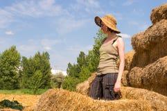 Hübsche Frau mit dem Hut, der in den Strohballen steht und weg an einem sonnigen Tag schaut Stockfotografie