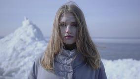 Hübsche Frau mit dem langen blonden Haar im warmen Mantel, der in der Kamerastellung auf dem Gletscher schaut Überraschende Ansic stock footage