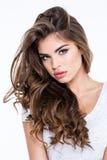 Hübsche Frau mit dem langen gelockten Haar, das Kamera betrachtet Stockfoto