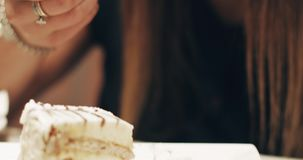 Hübsche Frau mit dem langen Haar isst einen köstlichen Kuchen an einem Restaurant stock footage