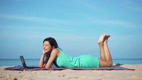 Hübsche Frau mit dem Laptop, der auf Strand sich entspannt stock footage