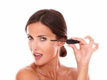 Hübsche Frau mit der Wimperntusche, die ihr Weiblichkeit zeigt Stockbild