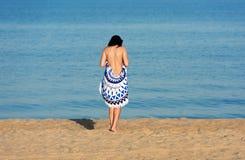 Hübsche Frau mit einer runden Strandtapisserie der Mandala in der Küste Lizenzfreie Stockbilder