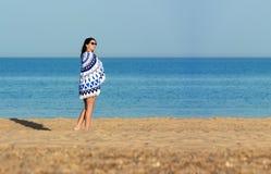 Hübsche Frau mit einer runden Strandtapisserie der Mandala in der Küste Stockfotos