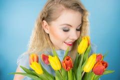 Hübsche Frau mit rotem gelbem Tulpenbündel Lizenzfreie Stockbilder