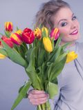 Hübsche Frau mit rotem gelbem Tulpenbündel Lizenzfreies Stockfoto
