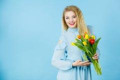 Hübsche Frau mit rotem gelbem Tulpenbündel Lizenzfreie Stockfotografie
