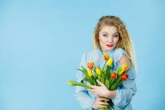 Hübsche Frau mit rotem gelbem Tulpenbündel Stockfotografie