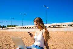 Hübsche Frau mit schönem Lächeln auf dem Gesicht und dem langen Haar, die in der Hand Handy halten und on-line-Video aufpassen lizenzfreie stockfotografie