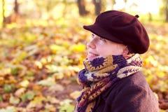 Hübsche Frau mit Schutzkappen- und Herbstblathintergrund Stockfoto