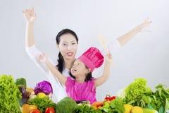 Hübsche Frau mit Tochter und Gemüse stockfotos