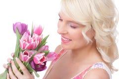 Hübsche Frau mit Tulpen im Frühjahr Stockbilder