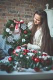 Hübsche Frau mit Weihnachtsbaum-Kranz zu Hause stockfoto