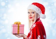 Hübsche Frau mit Weihnachtsgeschenk im roten Hut Lizenzfreies Stockbild