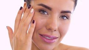Hübsche Frau reibt Creme in ihrer Gesichtshaut stock video footage